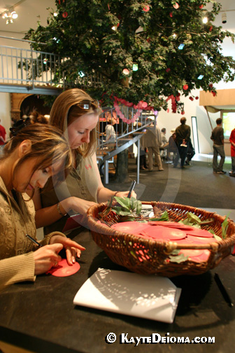 Two women write wishes on pomegranate shaped paper to tie onto the pomegranate tree at the Jewish Museum Berlin, Germany.