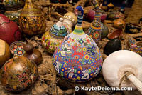 A colorfully beaded gourd rests among a mountain of painted and plain vessels at the Mexican Folk Art Museum in Cancun.