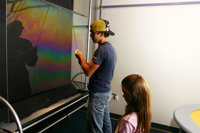 Becca watches as Derick creates a wall of soap bubble at the Great Lakes Science Center.
