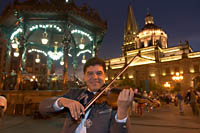 Violinist Sergio Caratachea Alvarez of the Mariachi Internacional de Guadalajara on Plaza de Armas with the kiosko and cathedral lit up in the background. Guadalajara, Jalisco, Mexico