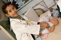 A young girl in a lab coat administers a shot to a doll in the Maroma section of Trompo Magico Interactive Museum.