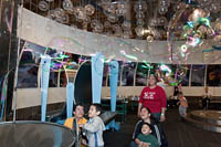 A boy turns a wheel that creates a giant bubble that spreads around the room in the Burbujas section of Trompo Magico.