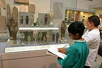 Two boys sketch Egyptian artifacts for a school assignment at the British Museum in London.