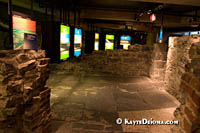 Artifacts are displayed in cases with colored panels among the walls of early Montreal buildings. Š Kayte Deioma