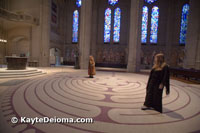People walk in meditation on the indoor wool tapestry labyrinth at Grace Cathedral in San Francisco, CA.