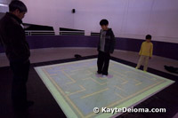A boy uses his weight to move a virtual marble around the MetaField Maze at the Zeum in San Francisco.